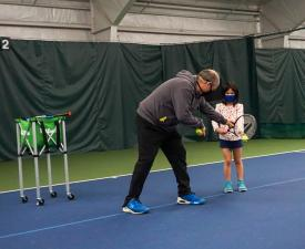 teaching tennis to child player